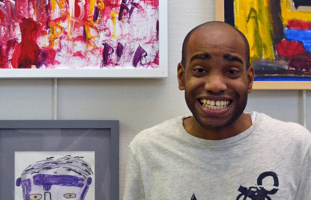 Man smiling in front of framed art pieces.